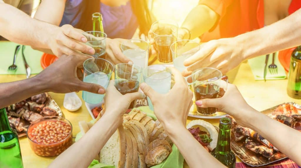 A group of people toasting alcoholic drinks at a barbecue