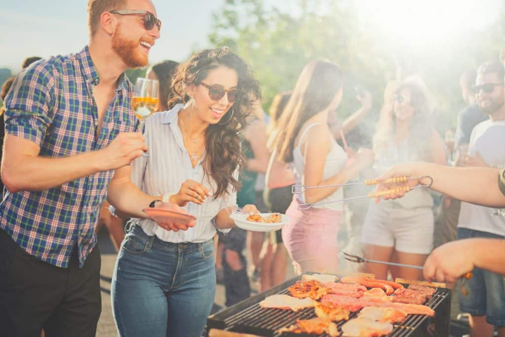 A group of people gathered around a barbecue grill