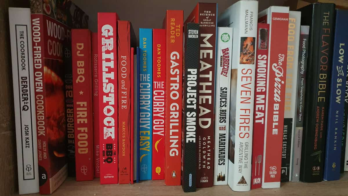 A line of various stood up BBQ cookbooks, looking at the spines