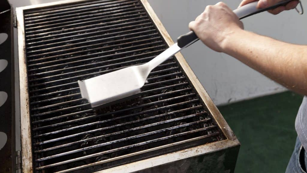 A man scrubbing grill grates with a brush