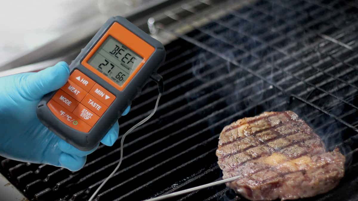 An orange digital grill and smoker thermometer reading the temperature of some meat