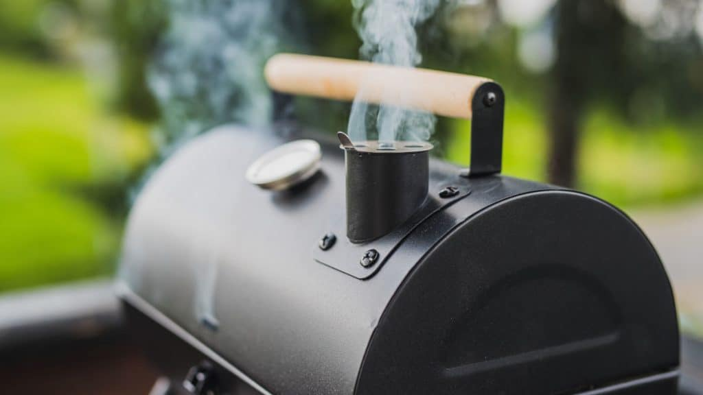 An offset smoker with smoke coming out of the chimney