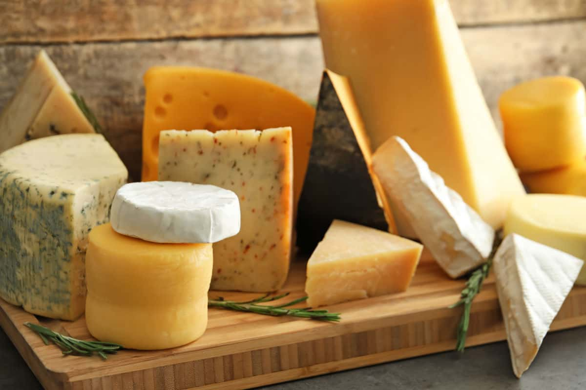A selection of different cheeses on a chopping board