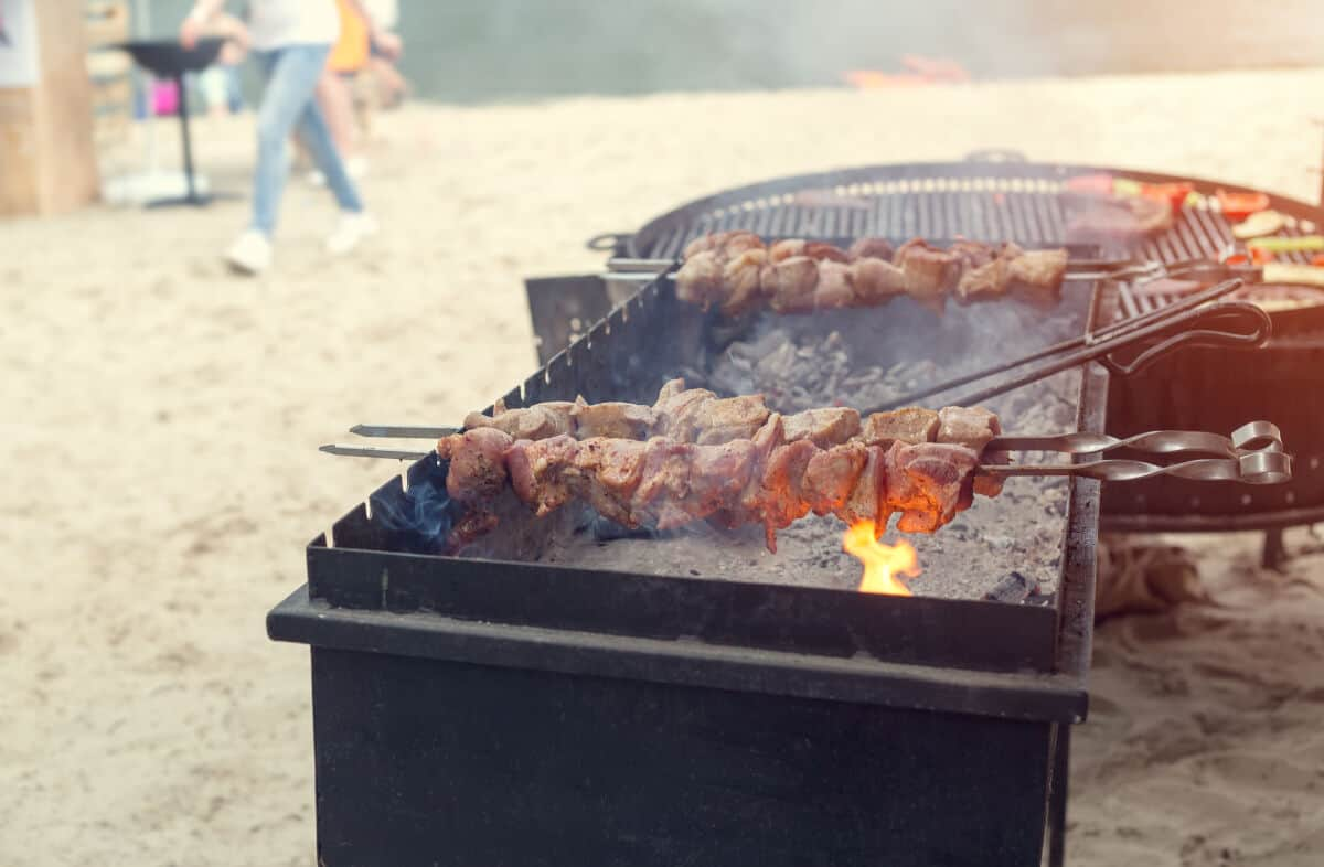 Two charcoal grills on a sandy beach