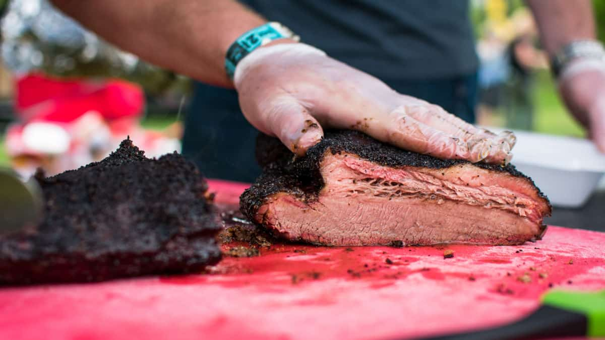 A gloved hand squashing cooked brisket onto a red cutting board