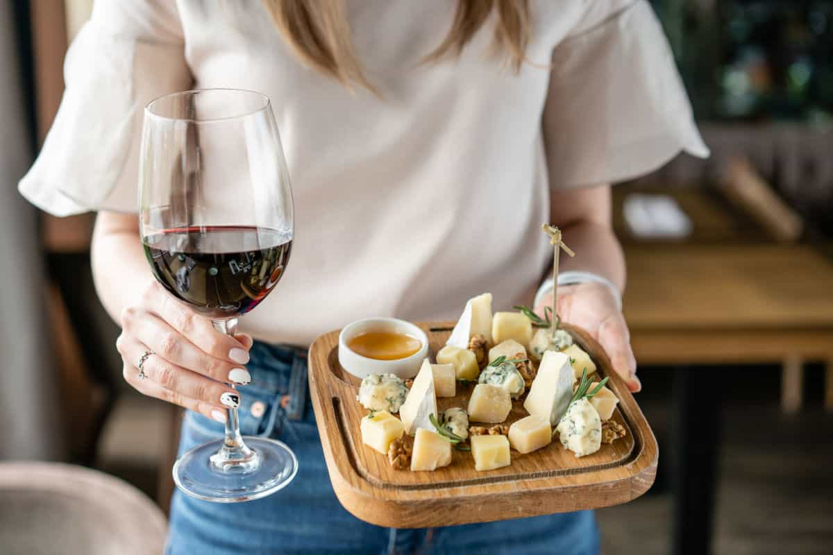 A woman carrying a cheese board and a glass of wine