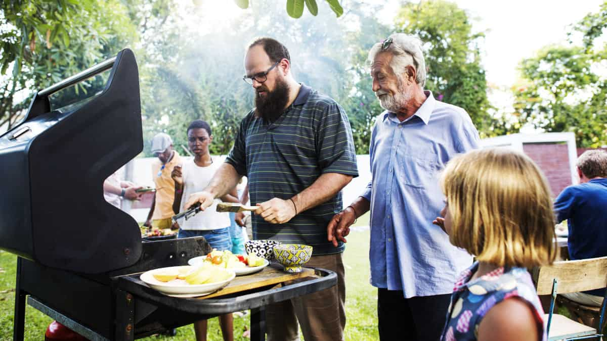 A family gathered around a BBQ while a man is cooking