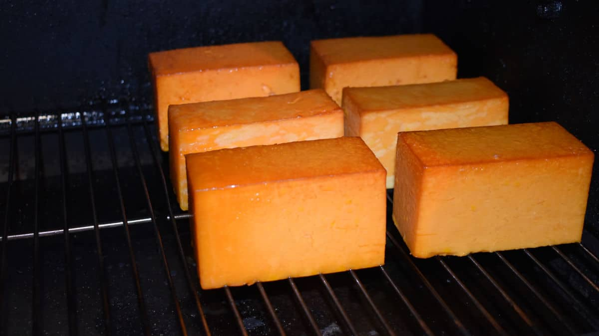 six blocks of cheese being cold smoked in a smoker