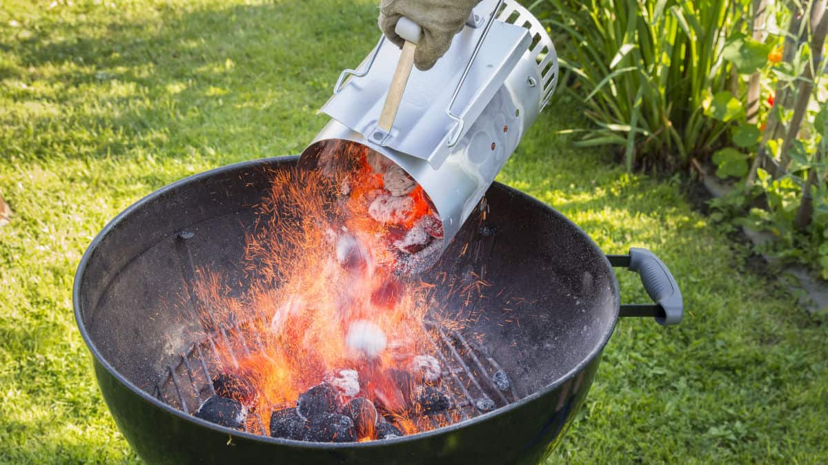 A charcoal chimney of hot coals being poured into a charcoal grill