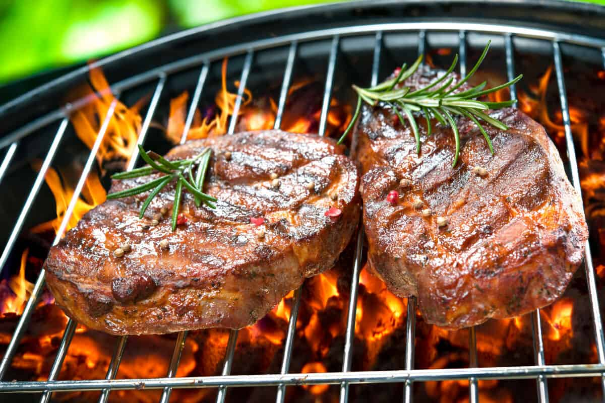 Two steaks with sprigs of rosemary on a charcoal grill