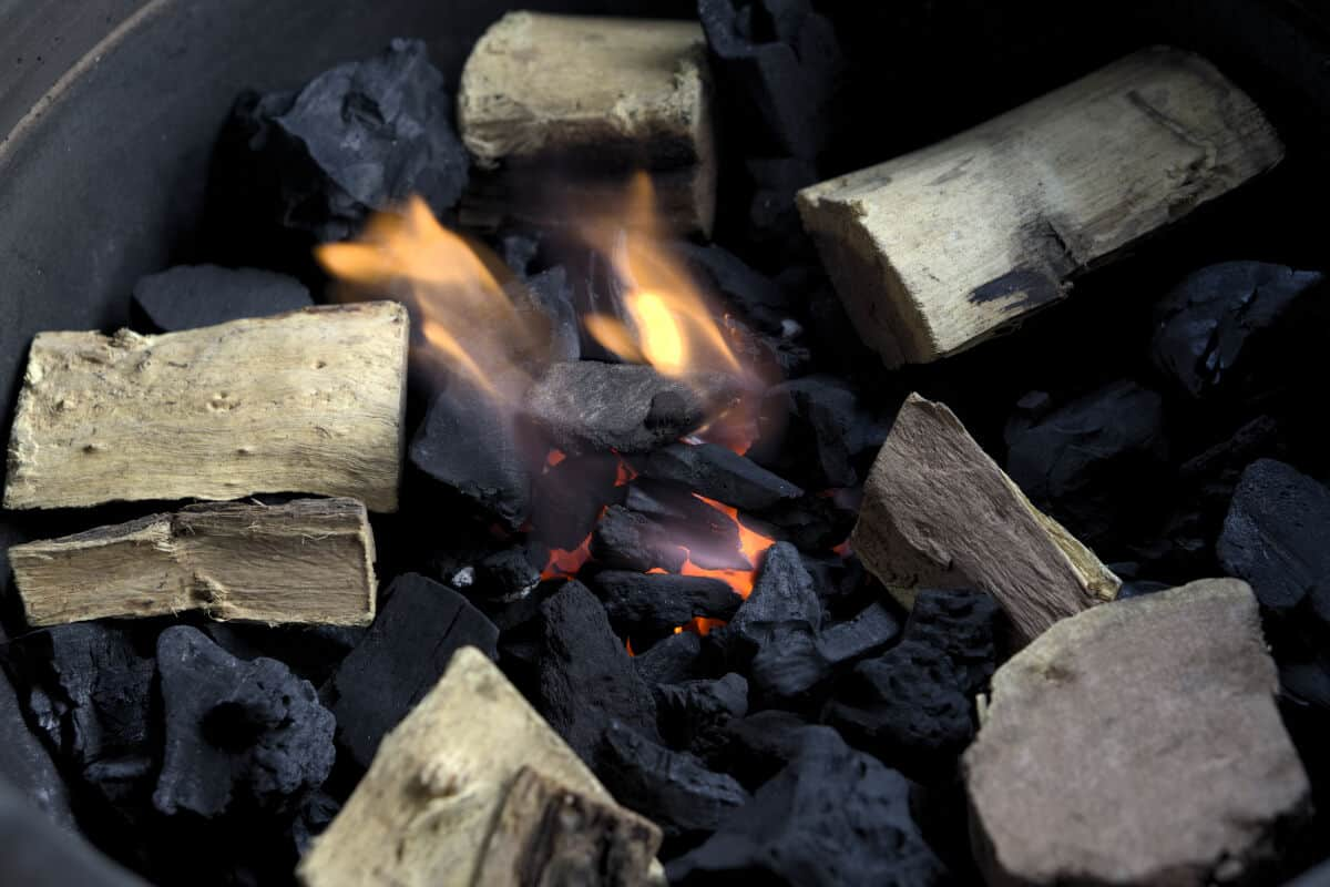 Burning charcoal with wood for smoking meat