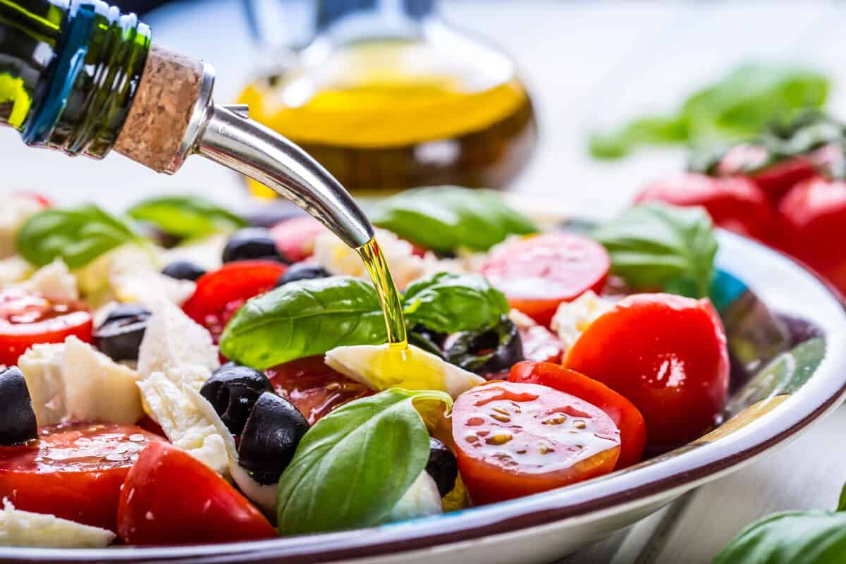 Close up of a dressing being poured over a brightly colored salad of tomatoes, cheese and basil
