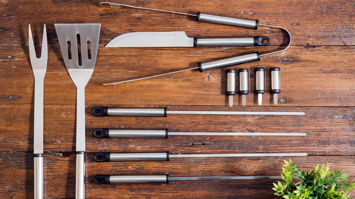 A set of bbq and grilling tools laid out on a wooden table