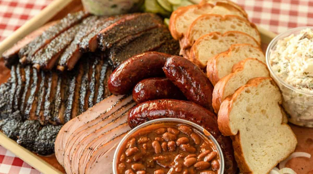 a barbecue platter of mixed meats including brisket, ribs, sausage and sides