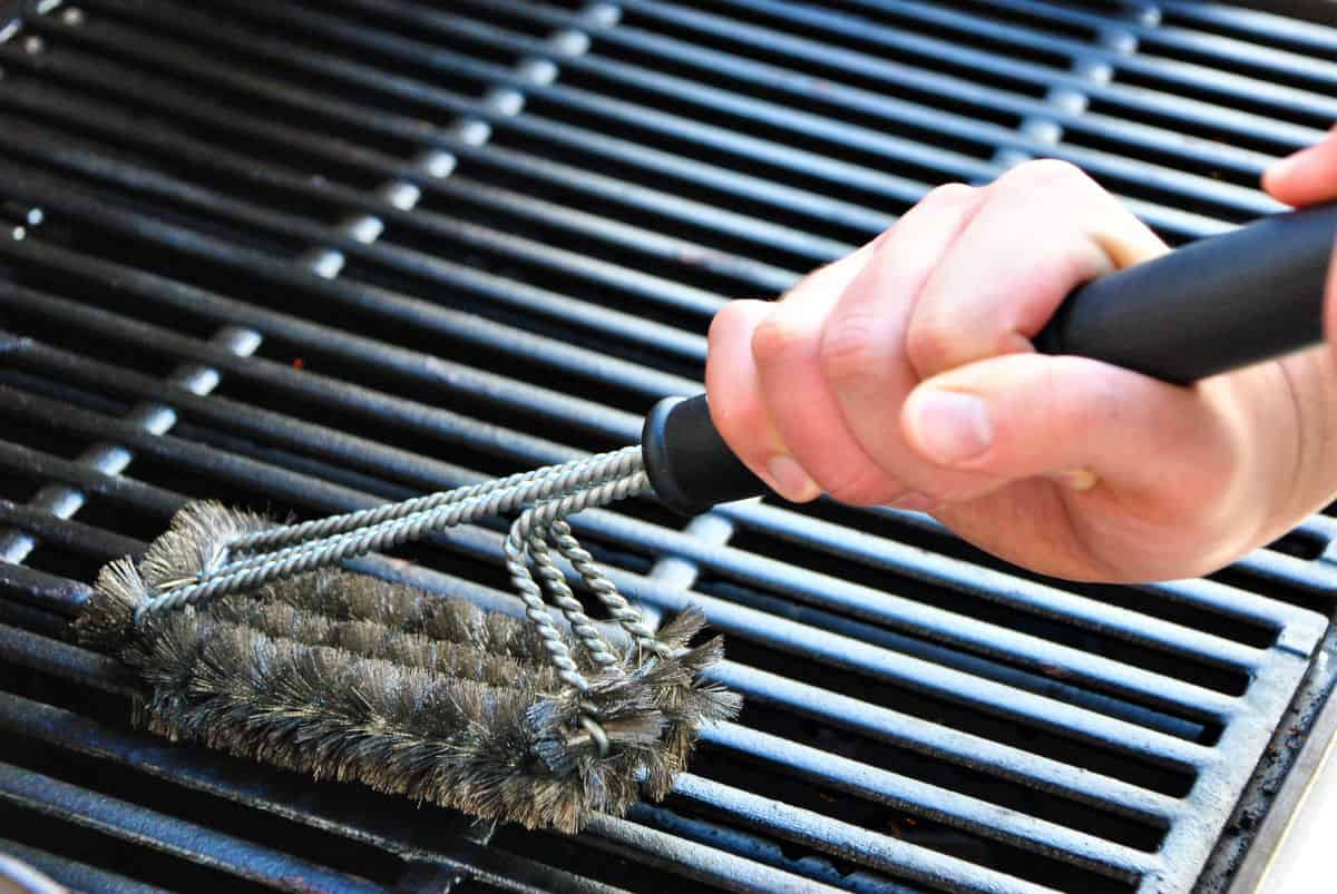 A grill brush being used on some grates