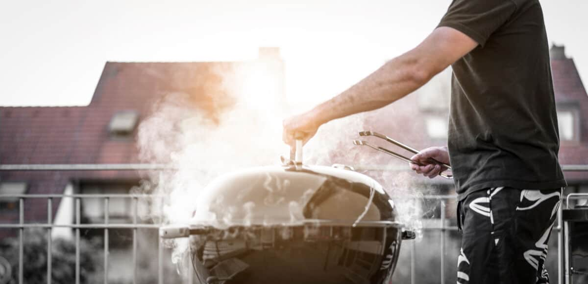 A man removing the lid form a heavily smoking grill