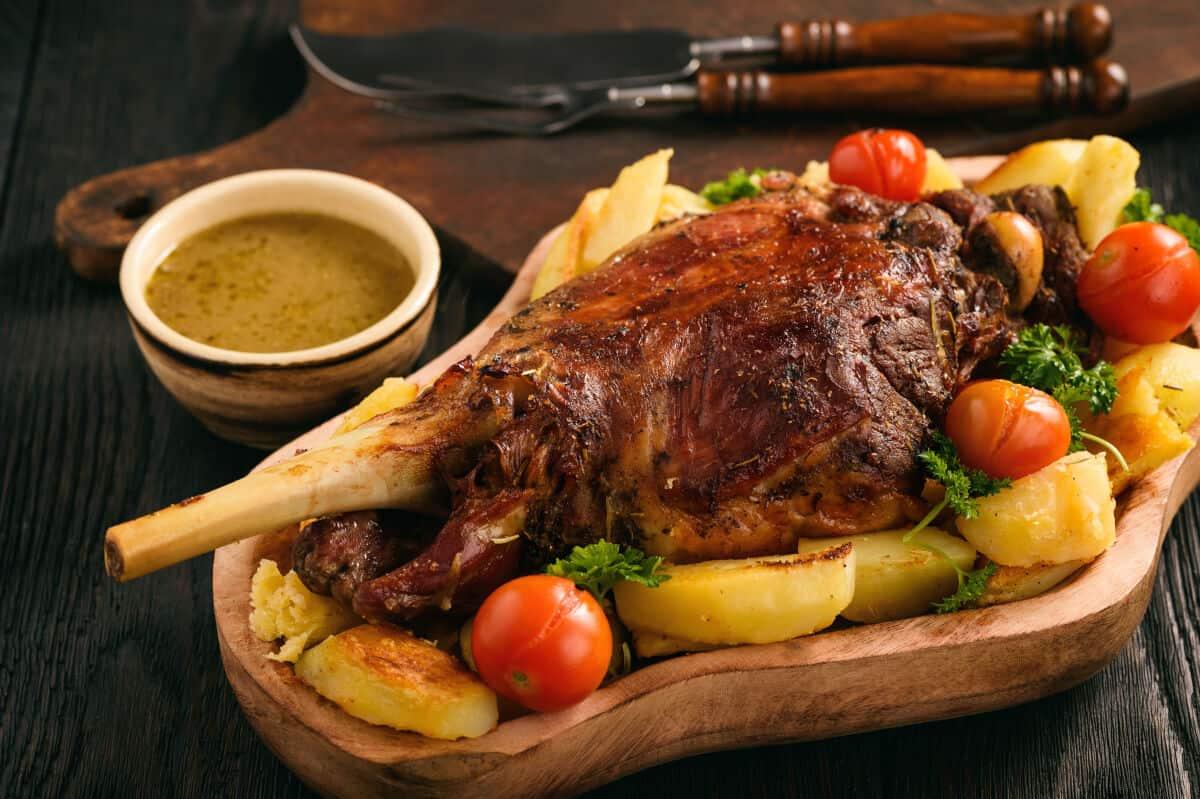A beautiful looking smoke roasted lamb leg surrounded by roasted veg