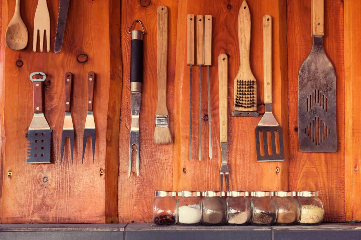 Lots of grill tools hanging on a wooden wall
