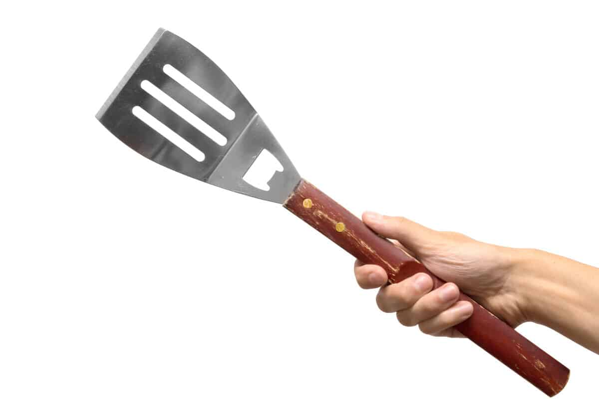 A hand holding a grilling spatula isolated on white