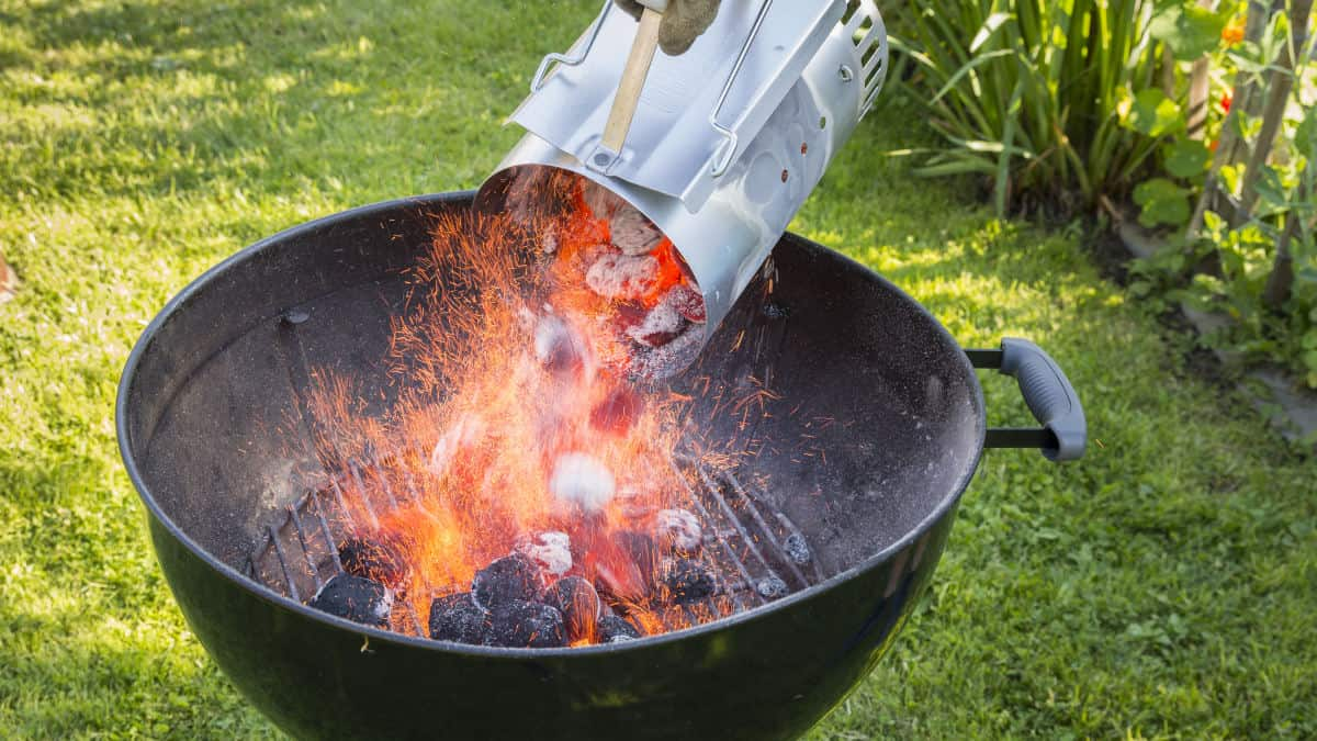 A charcoal chimney starter being poured out into a kettle grill