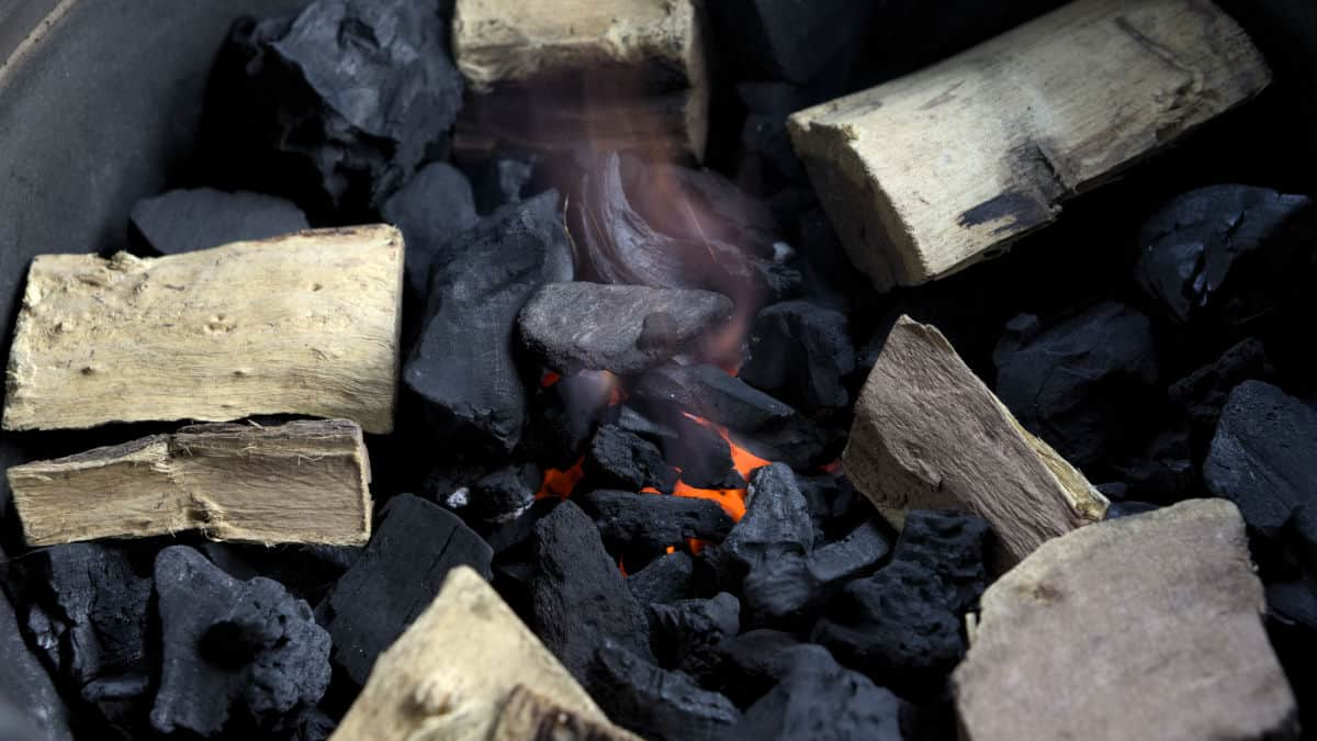 Close up of lit charcoal with smoking wood on top, laid out in a circle