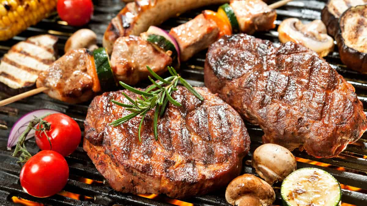 Close up of steak, kebabs and vegetables being grilled