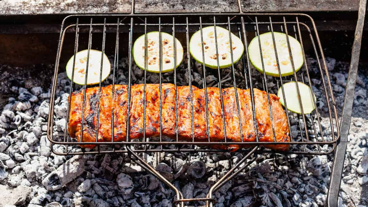 A grill basket over charcoal with ribs and courgette slices