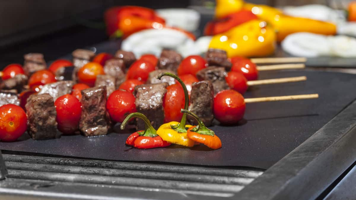 Skewered meat and veg on a grill mate on a BBQ
