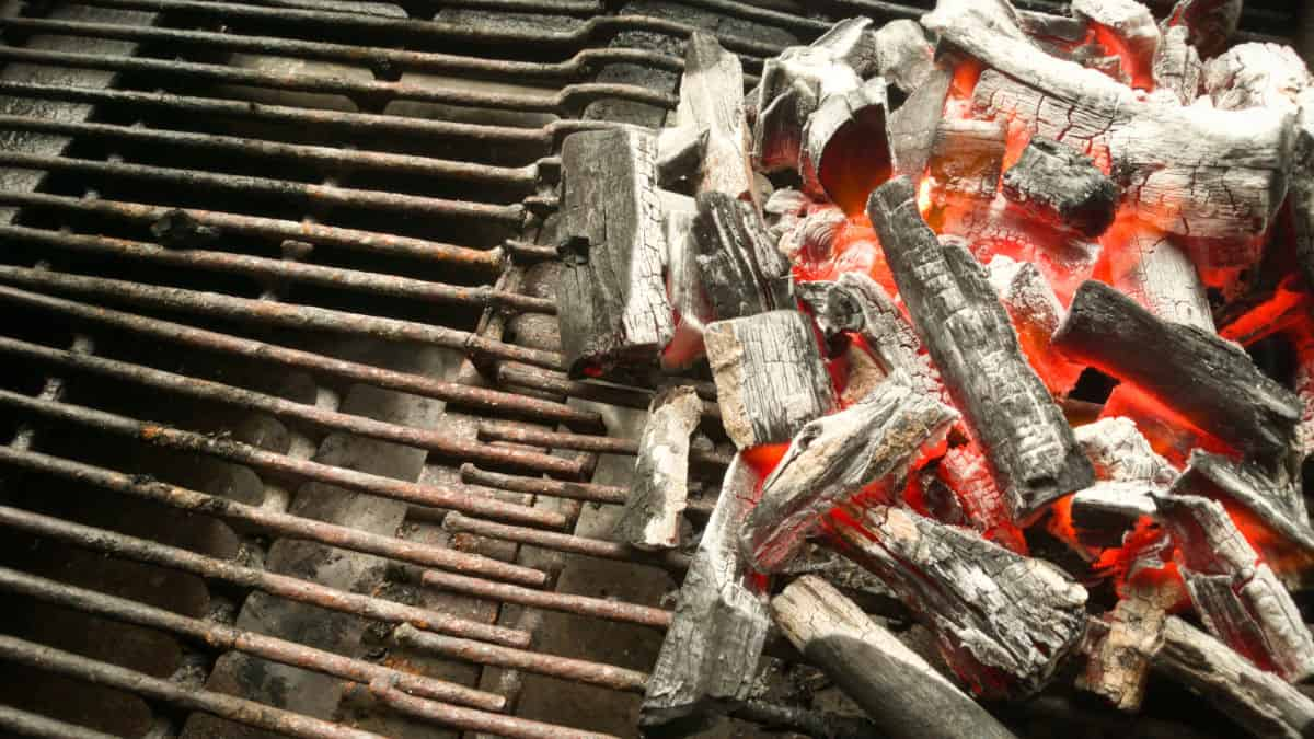 Burning lump charcoal banked up on half a charcoal fire grate