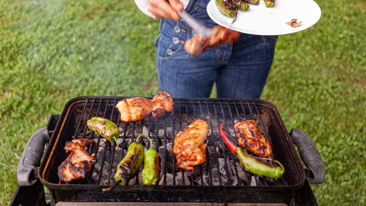 Weber go anywhere grill cooking meat and peppers, with a someone helping themselves to food