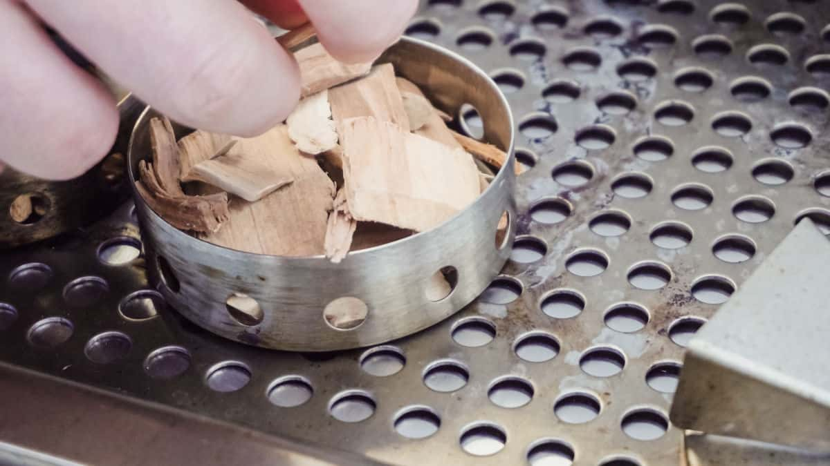 A round wood chip smoker box being filled on a gas grill