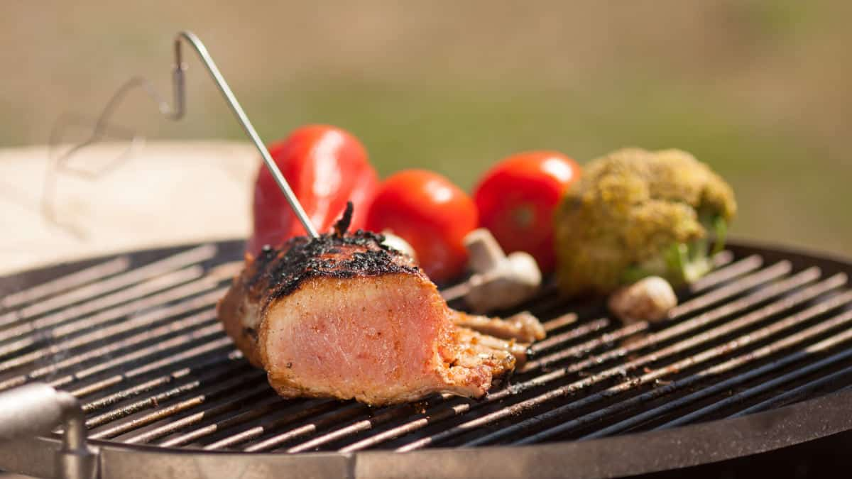 A remote Bluetooth thermometer probe stuck into some meat on a grill next to some vegetables