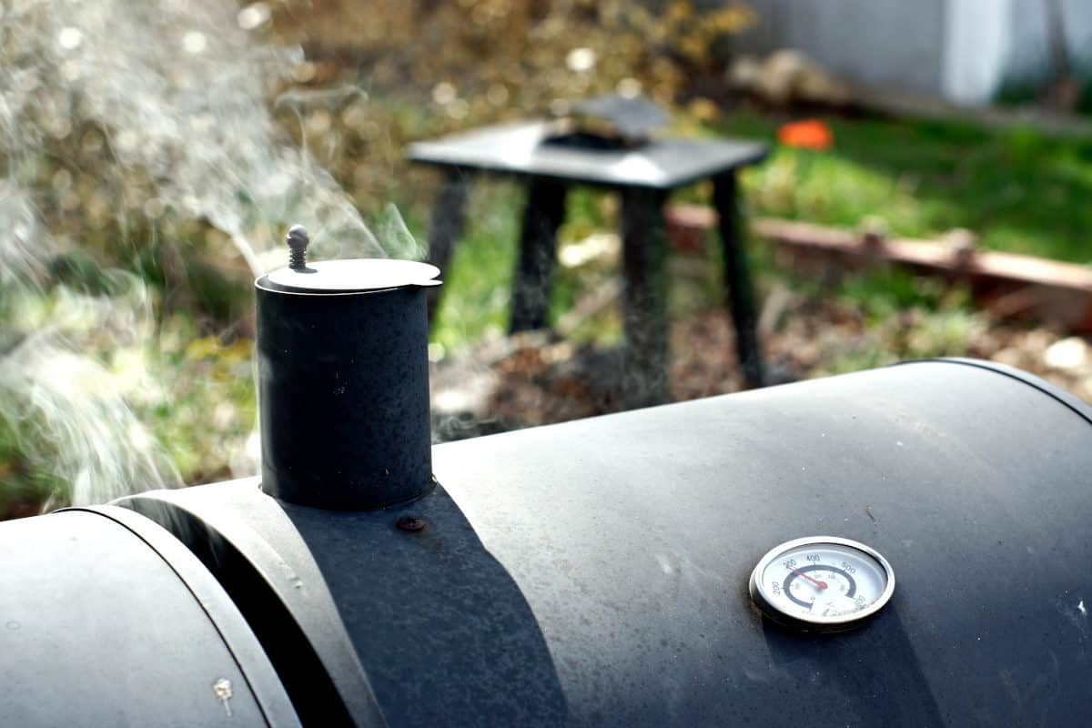 A barrel type smoker, with chimney, and a thin wisp of smoke coming out