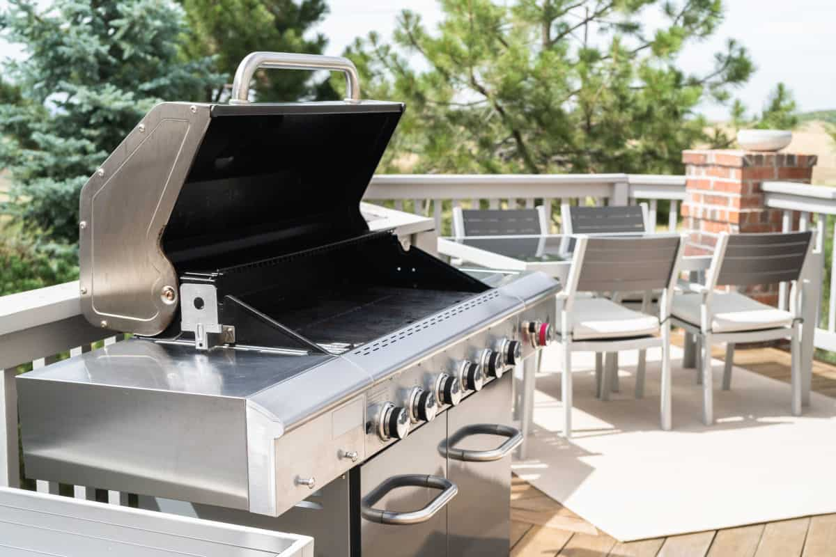Side view of a gas grill, lid open on a sunny patrio