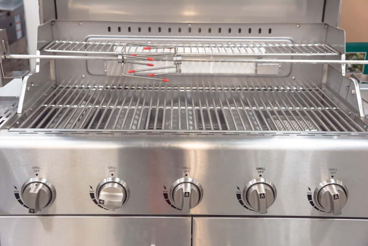 Close up of a gas grill llid open, showing rotisserie attachment