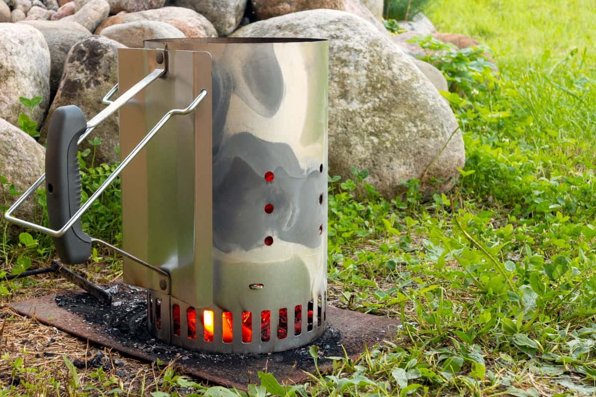 A charcoal chimney starter sat on a metal plate, with paper burning to light the coals