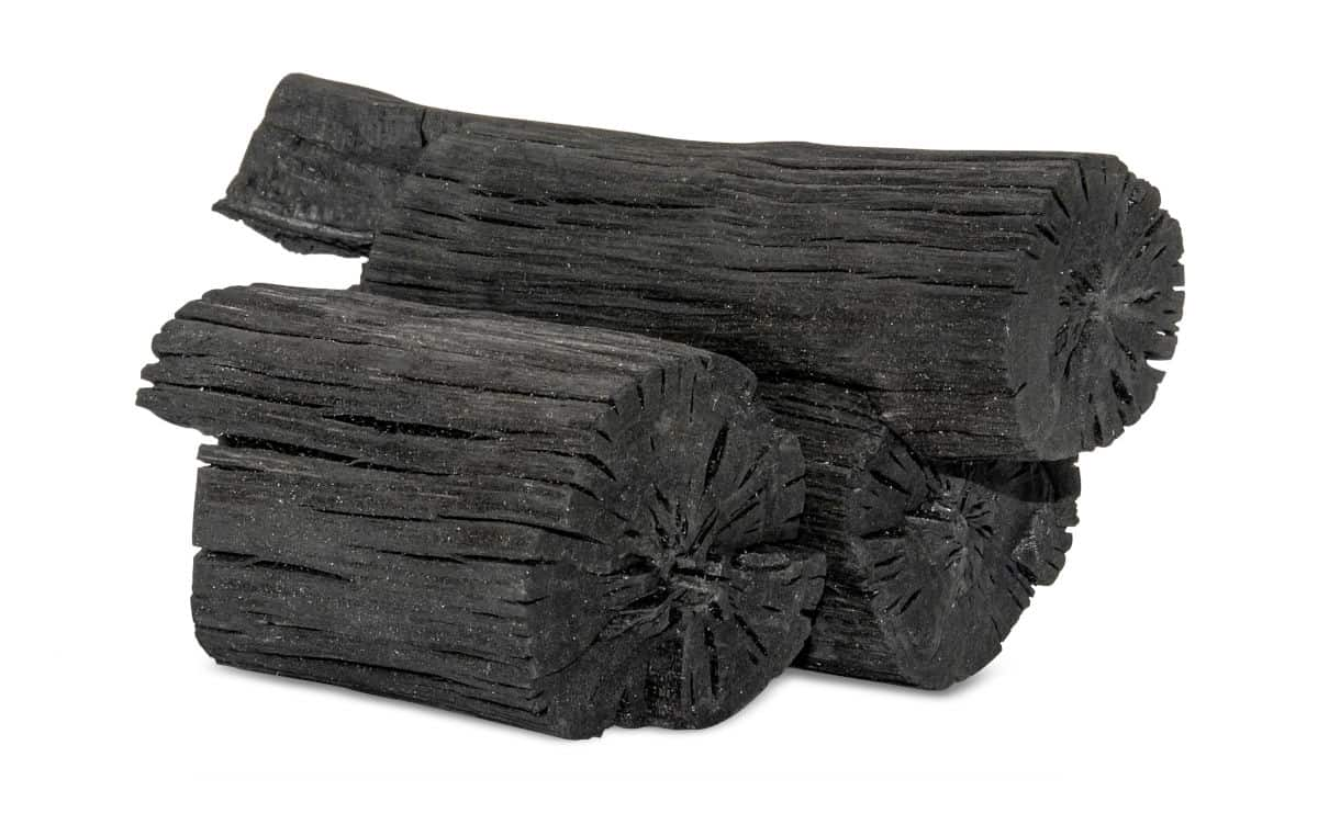 2 log shaped lumps of hardwood lump charcoal isolated on white