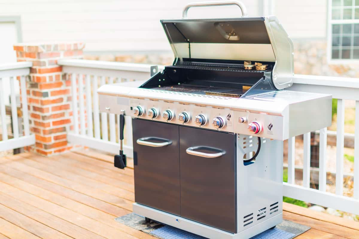 A black and silver gas grill on a wooden decking