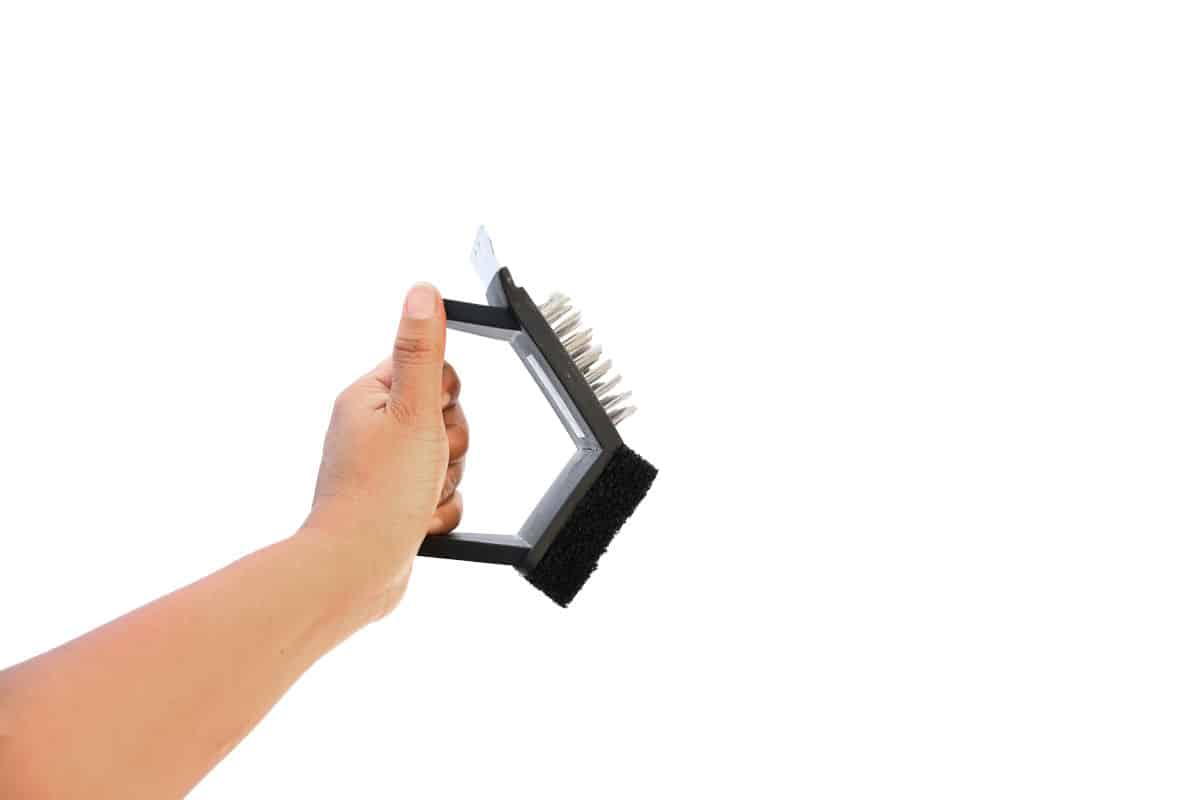 A 3 sided grill brush being held by a man, isolated on white