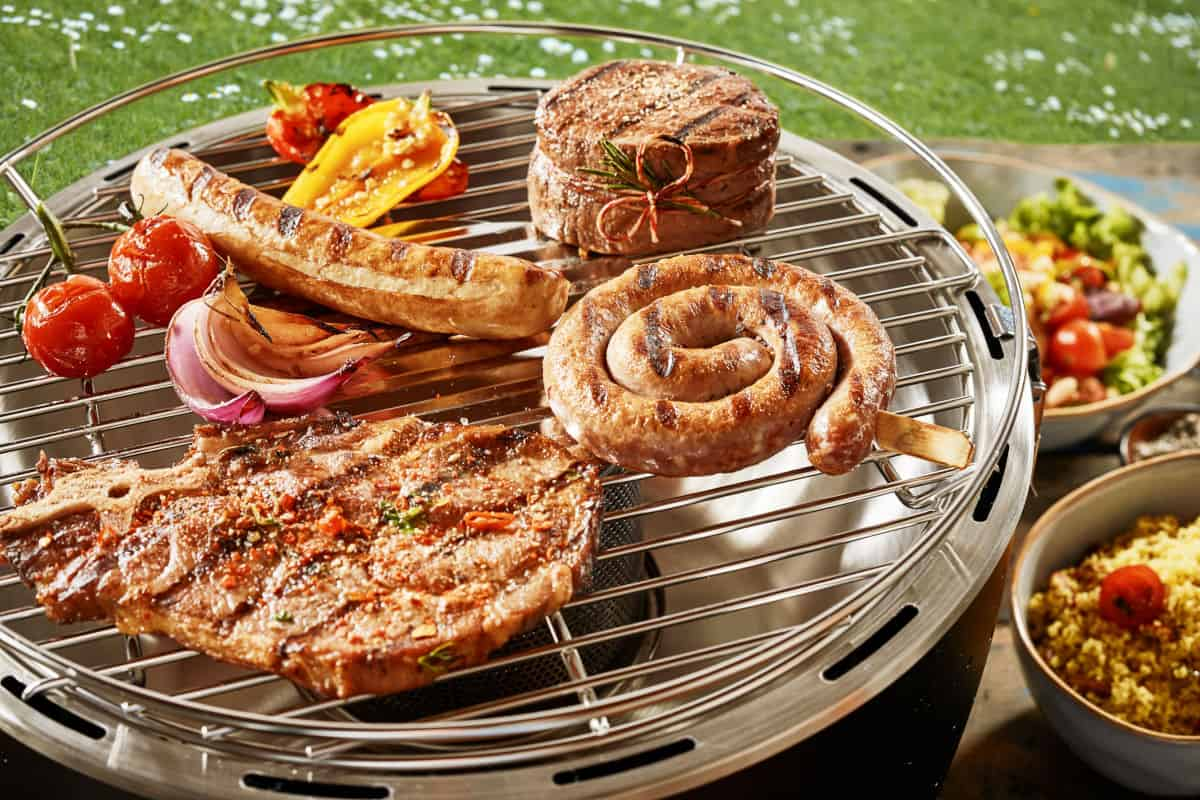 Sausages and steak being grilled on a tabletop gas grill