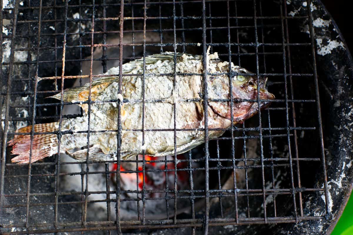 Fish in a grill basket over charcoal