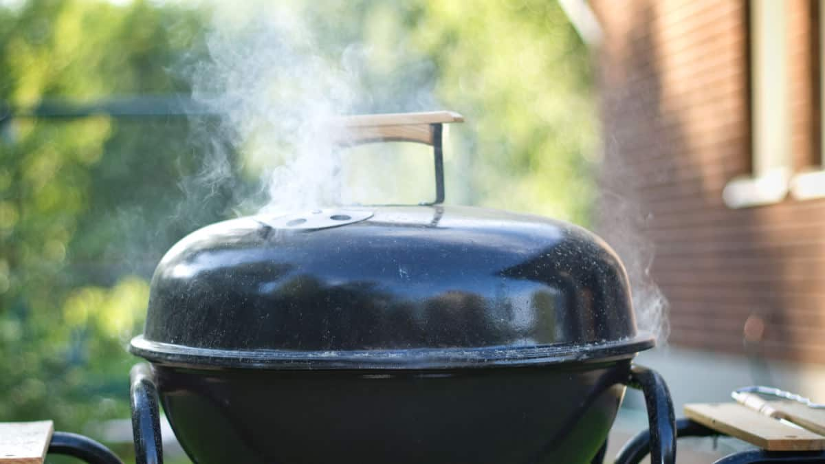 Close up of a charcoal grill, with lid on and smoke billowing from the top vent