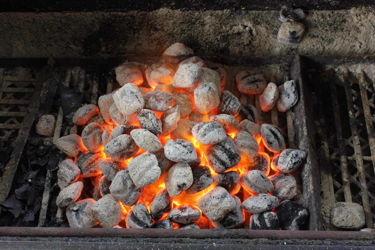 A pile of lit briquettes in a charcoal barbecue