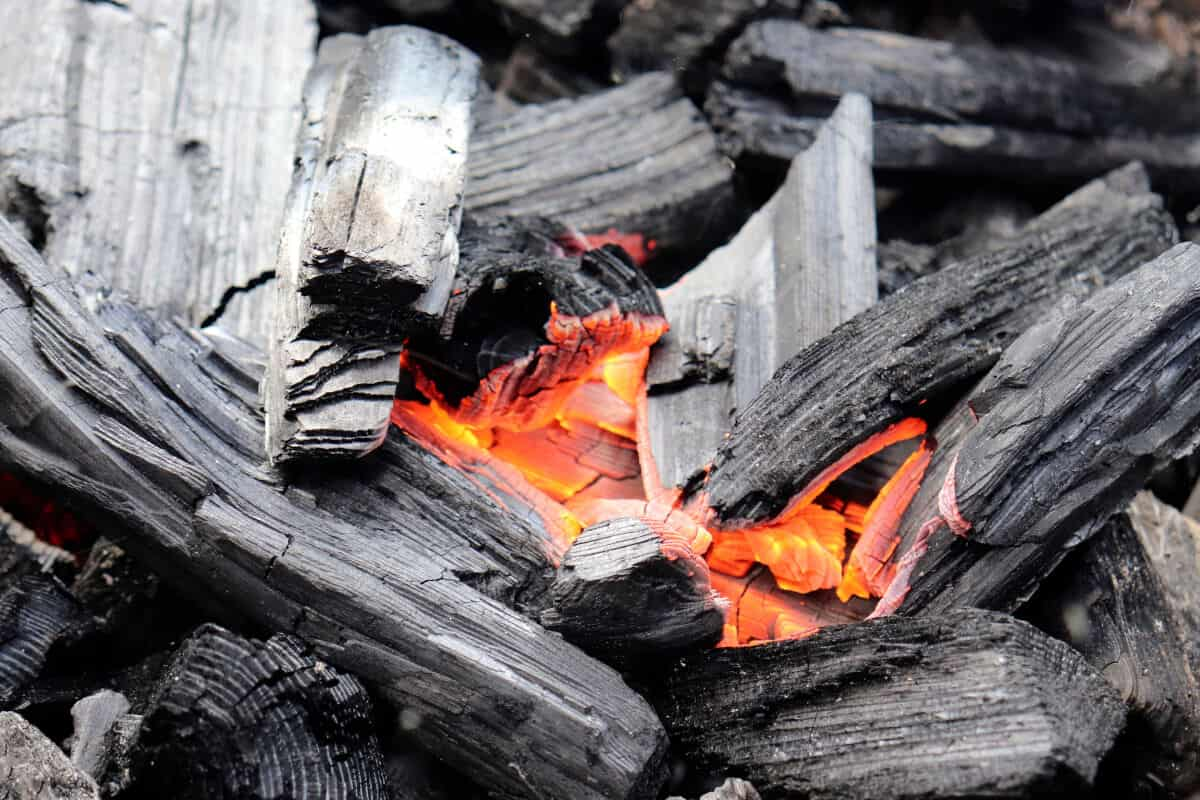 A pile of lumpwood charcoal, that is lit and burning just in the center