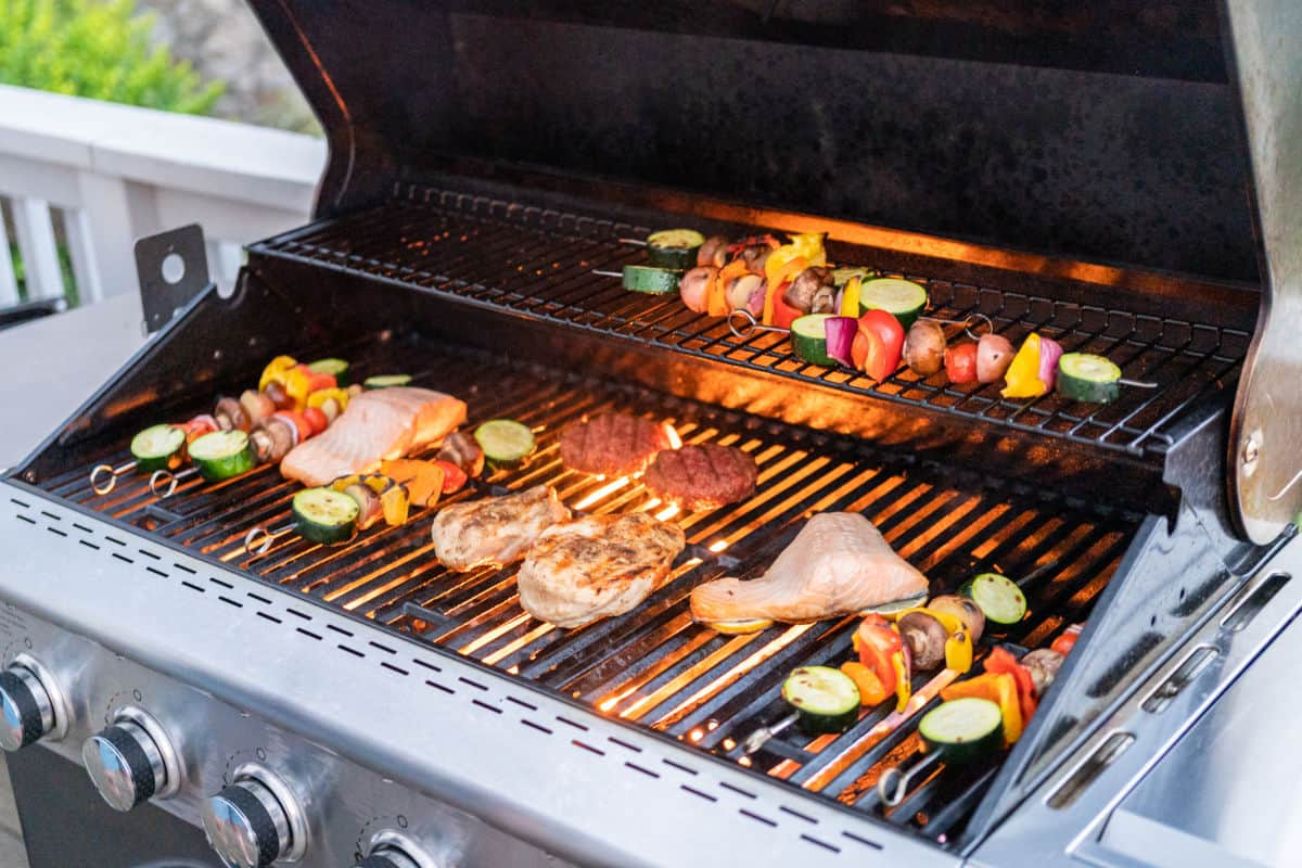 An outdoor gas grill with all burners on, grilling many different meats and kebobs