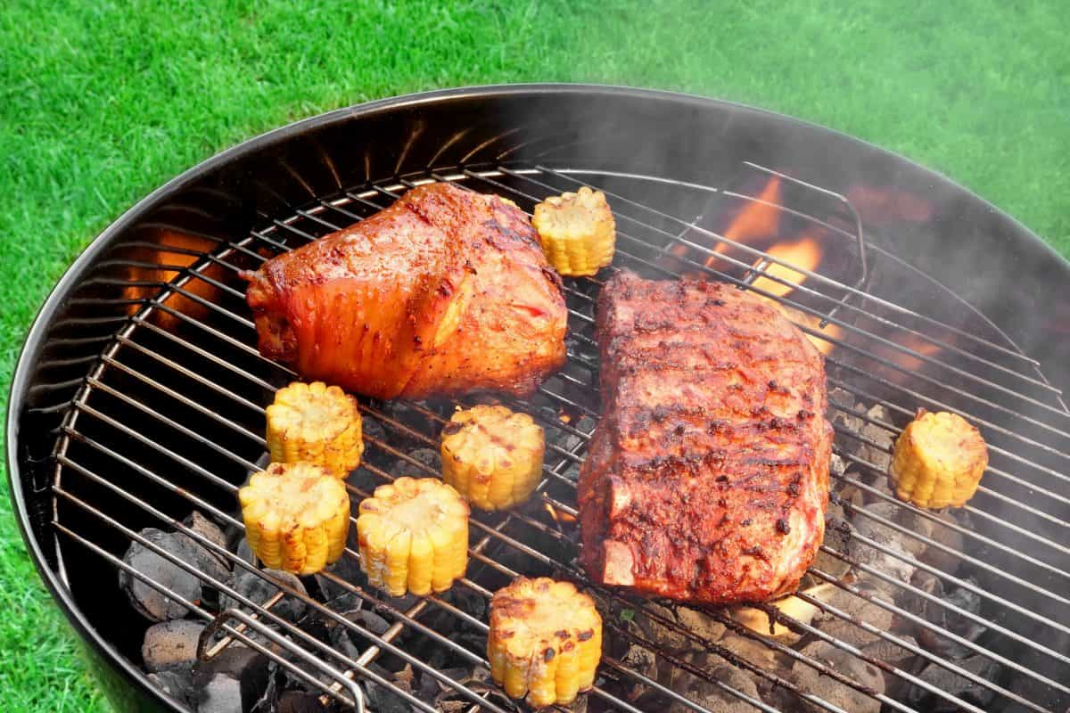 A charcoal kettle grill with 2 pieces of meat and some sweetcorn sections being grilled
