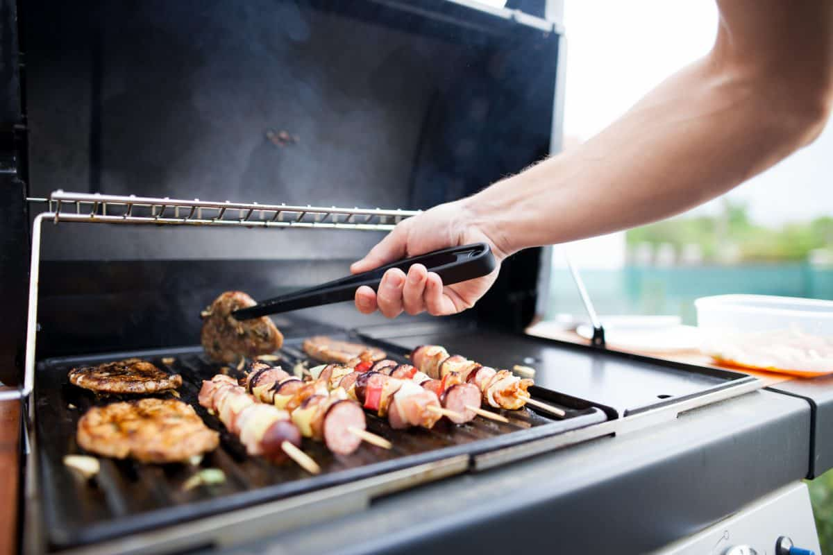A man turning a burger on a gas grill that's grilling burgers and kebabs