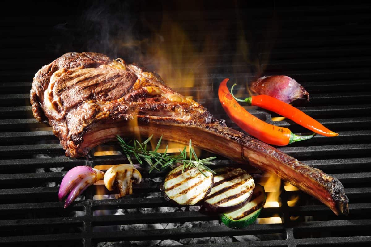 A tomahawk steak on a charcoal grill with some vegetable slices and a chili