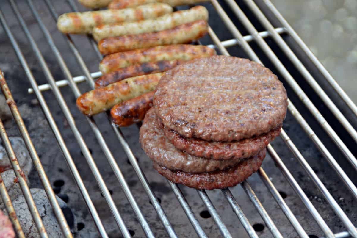 Burgers and sausages being grilled indirect on a charcoal grill