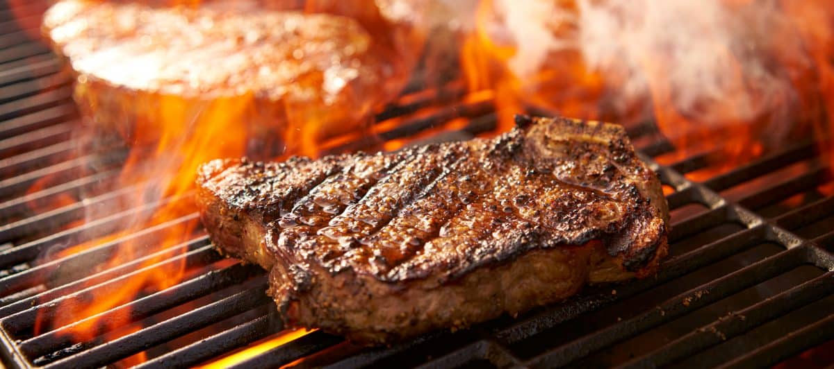A steak being seared on a fiery hot grill